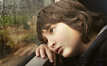 boy with head lying on a window sill