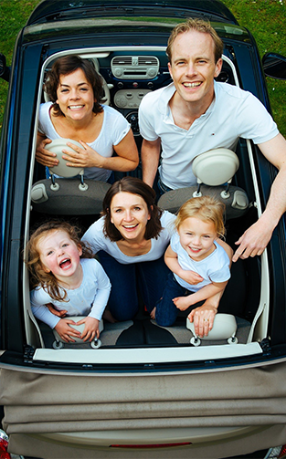 family of four in a convertible car